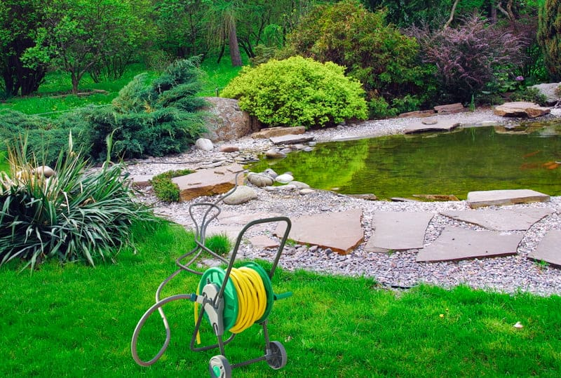 Garden Hose Reel in Yard Near Pond